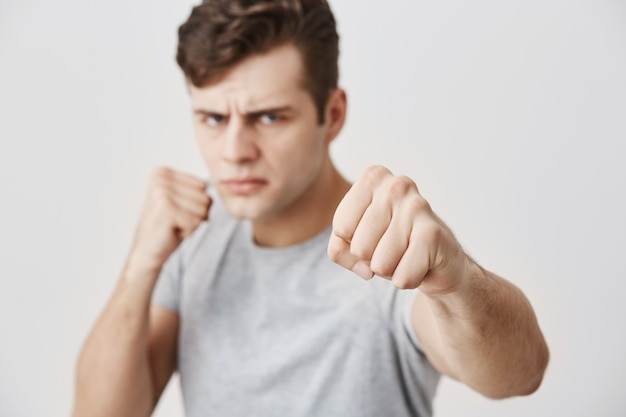 Verärgerter, aggressiver junger kaukasischer mann, der in einer verteidigungsposition steht, die fäuste geballt hält, einen selbstbewussten blick hat, bereit ist, sich zu verteidigen und für seine rechte eintritt