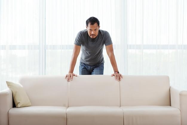 Verärgerter asiatischer mann, der hinter couch steht, auf ihr sich lehnt und kamera betrachtet