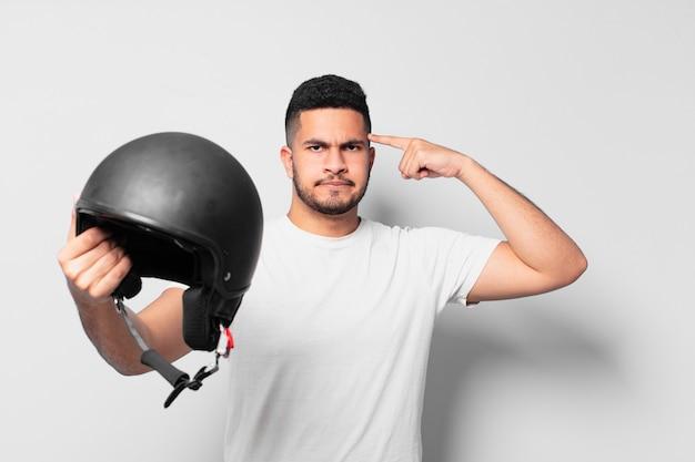Verärgerter ausdruck des jungen hispanischen mannes. motorradfahrerkonzept