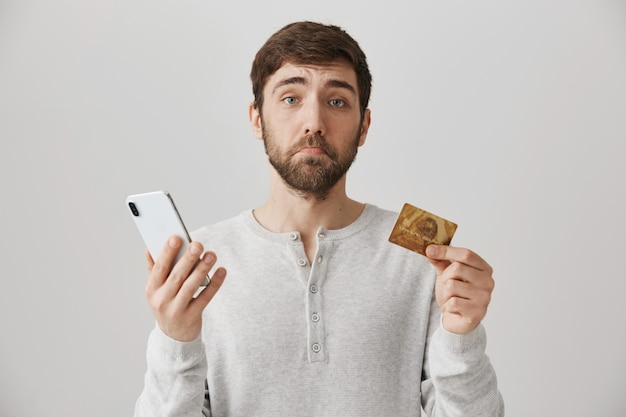 Verärgerter bärtiger kerl mit kreditkarte und smartphone