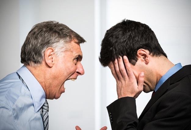 Verärgerter chef, der zu einem angestellten schreit