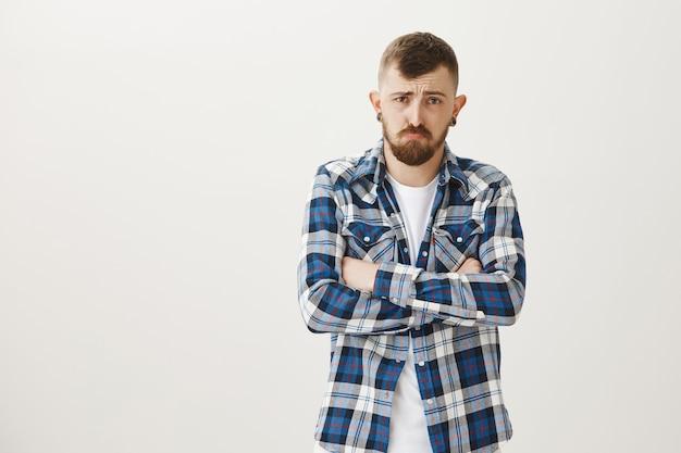 Verärgerter düsterer kerl, der sich beleidigt und traurig fühlt, verschränkt die brust