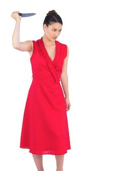 Verärgerter eleganter brunette im roten kleid, das messer hält