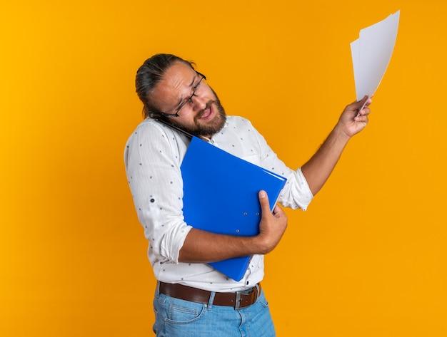 Verärgerter erwachsener gutaussehender mann mit brille, der ordner und dokumente hält und am telefon spricht, der isoliert auf orangefarbene wand schaut