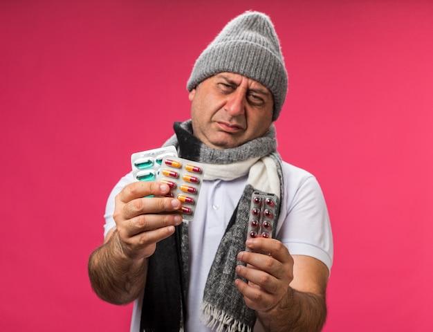 Verärgerter erwachsener kranker kaukasischer mann mit schal um den hals, der eine wintermütze trägt, die verschiedene medizinpackungen isoliert auf rosa wand mit kopienraum hält