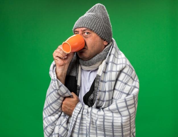 Verärgerter erwachsener kranker kaukasischer mann mit schal um den hals, der wintermütze trägt, eingewickelt in plaid, trinkt aus einer tasse isoliert auf grüner wand mit kopierraum