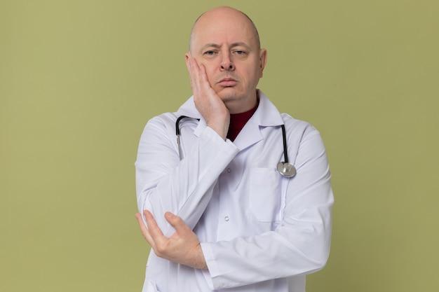 Verärgerter erwachsener mann in arztuniform mit stethoskop, der die hand auf sein gesicht legt und schaut