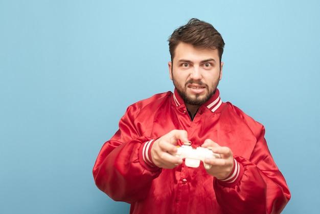 Verärgerter erwachsener mann mit bart spielt ein videospiel auf einer konsole mit einem gamepad in der hand auf blau
