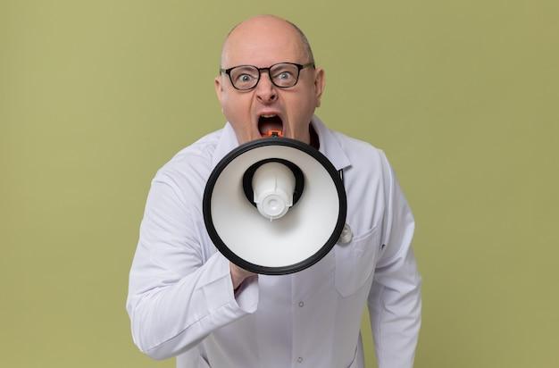 Verärgerter erwachsener mann mit brille in arztuniform mit stethoskop, das in den lautsprecher schreit