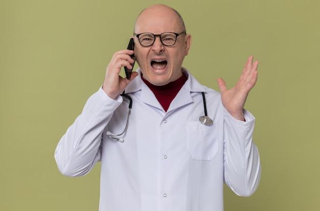 Verärgerter erwachsener mann mit brille in arztuniform mit stethoskop, der jemanden am telefon anschreit