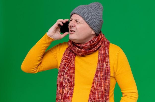 Verärgerter erwachsener mann mit wintermütze und schal um den hals, der am telefon spricht und auf die seite schaut