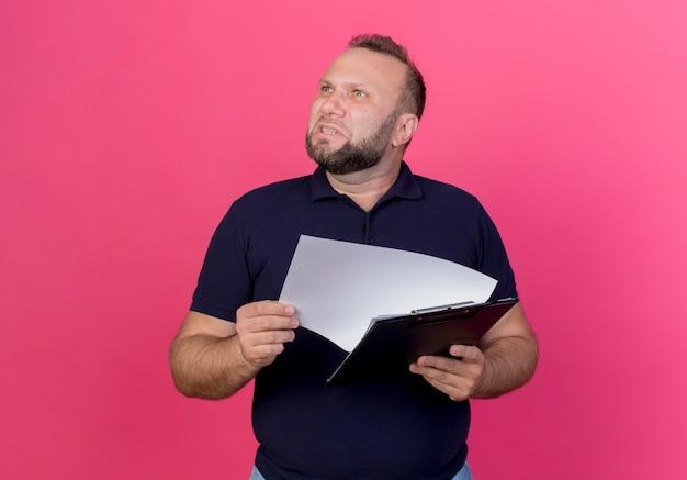 Verärgerter erwachsener slawischer mann, der zwischenablage hält und isoliert nach oben schaut