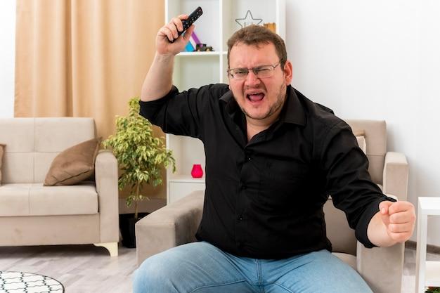 Verärgerter erwachsener slawischer mann in der optischen brille sitzt auf sessel, der faust hält und hand hebt, die tv-fernbedienung innerhalb des wohnzimmers hält