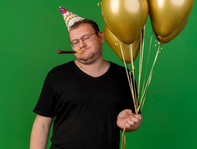 Verärgerter erwachsener slawischer mann in optischer brille mit geburtstagsmütze hält heliumballons, die partypfeife blasen