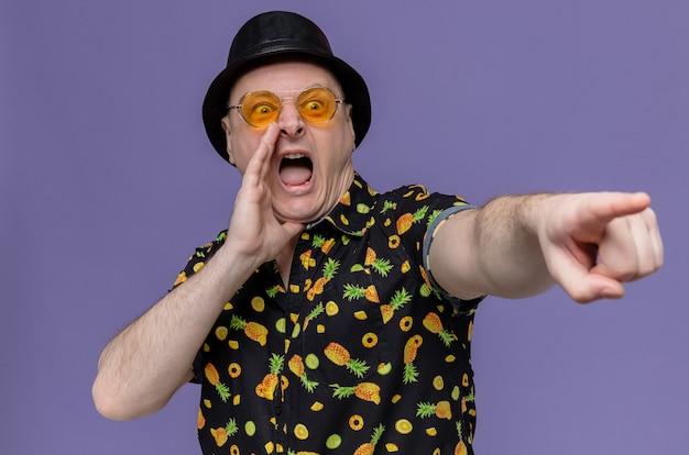 Verärgerter erwachsener slawischer mann mit schwarzem hut, der eine sonnenbrille trägt, die hand nah an seinem mund hält und auf die seite zeigt
