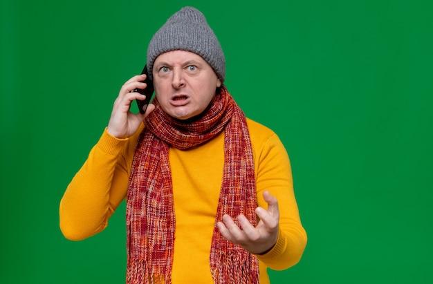 Verärgerter erwachsener slawischer mann mit wintermütze und schal um den hals, der am telefon spricht