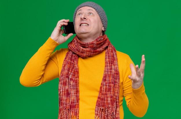 Verärgerter erwachsener slawischer mann mit wintermütze und schal um den hals, der o telefon spricht