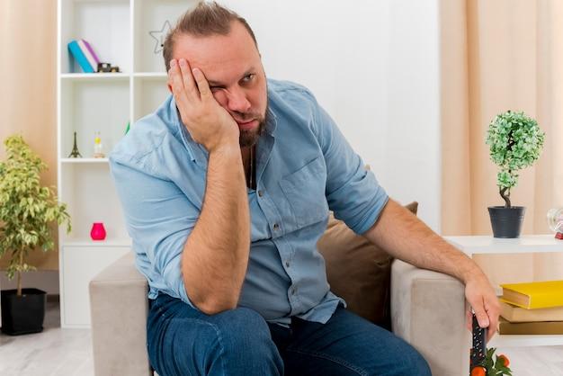Verärgerter erwachsener slawischer mann sitzt auf sessel, der hand auf gesicht setzt und seite innerhalb des wohnzimmers schaut