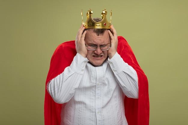 Verärgerter erwachsener slawischer superheldenmann im roten umhang, der brille und kronenhaltekopf trägt, der lokal unten auf olivgrüner wand mit kopienraum schaut