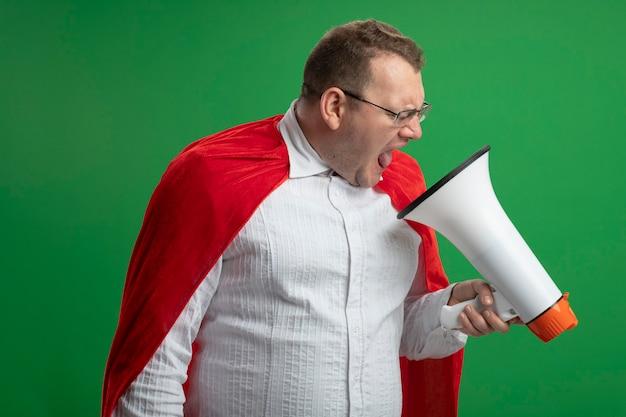 Verärgerter erwachsener slawischer superheldenmann im roten umhang, der die brille hält, die lautsprecher hält und schreit, isoliert auf grüner wand
