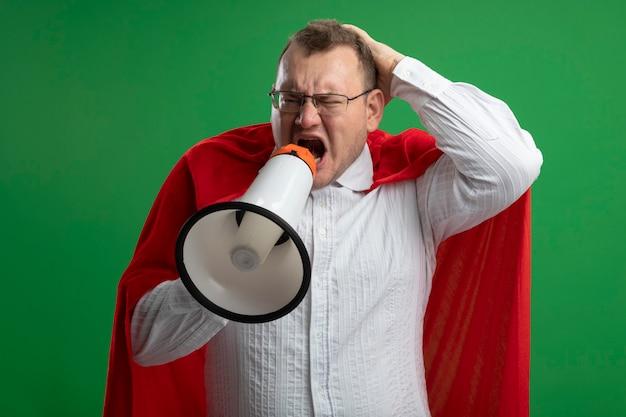 Verärgerter erwachsener slawischer superheldenmann im roten umhang, der die brille trägt, die hand auf kopf hält, die seite betrachtet, die im lauten lautsprecher lokalisiert auf grüner wand schreit