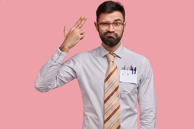 Verärgerter europäischer mann mit dicken borsten macht selbstmordgeste, schießt sich in die schläfe, hat unzufriedenen gesichtsausdruck, trägt formelles outfit
