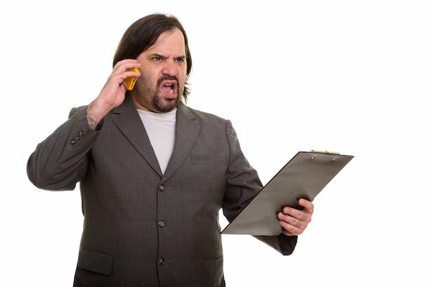 Verärgerter fetter kaukasischer geschäftsmann, der auf handy spricht, während er auf zwischenablage hält