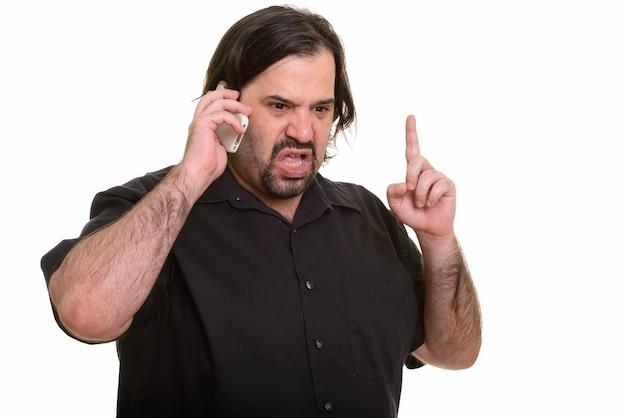 Verärgerter fetter kaukasischer mann, der auf handy spricht, während finger oben zeigt