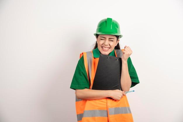 Verärgerter frauenkonstrukteur mit grünem helm, der mit klemmbrett steht foto in hoher qualität