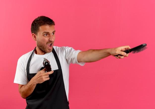 Verärgerter friseurmann in der schürze, der haarbürste und trimmer hält, die zur seite mit einer bürste zeigen, die unzufriedenes schreien und schreien über rosa wand steht