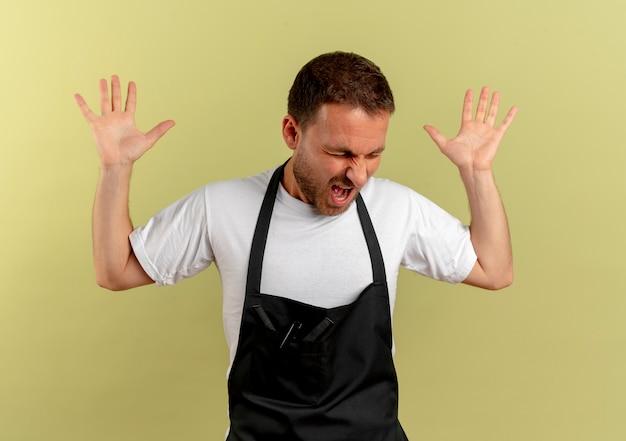 Verärgerter friseurmann in der schürze, der hände mit aggressivem ausdruck hebt und frustriert schreit, über heller wand stehend