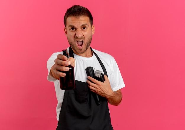Verärgerter friseurmann in der schürze, die haarbürste und trimmer hält, die nach vorne mit spray zielen, das über rosa wand steht