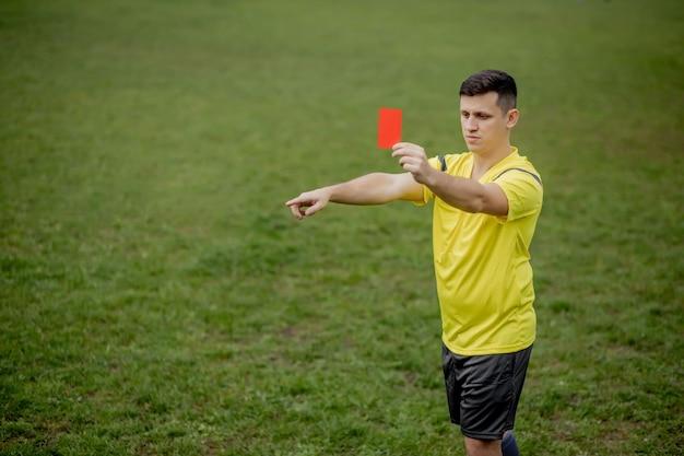 Verärgerter fußballschiedsrichter, der eine rote karte zeigt und mit der hand auf den elfmeter zeigt.