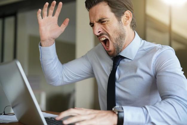 Verärgerter geschäftsmann, der geduld verliert und am laptop im modernen büro schreit