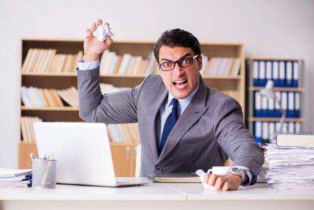 Verärgerter geschäftsmann, der im büro arbeitet