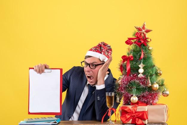 Verärgerter geschäftsmann der vorderansicht, der am tisch nahe weihnachtsbaum sitzt und auf gelbem hintergrund präsentiert