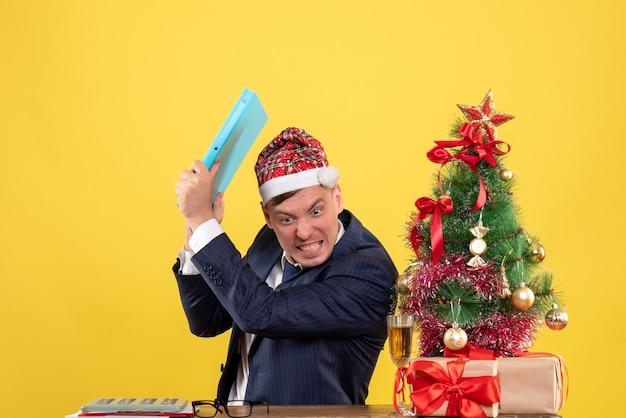 Verärgerter geschäftsmann der vorderansicht, der dokument weg von der tabelle nahe weihnachtsbaum und geschenken auf gelbem hintergrund wirft
