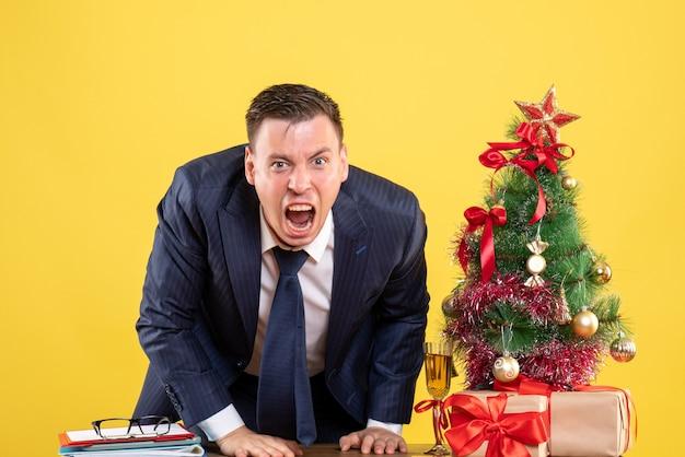 Verärgerter geschäftsmann der vorderansicht, der nahe weihnachtsbaum steht und auf gelbem hintergrund präsentiert