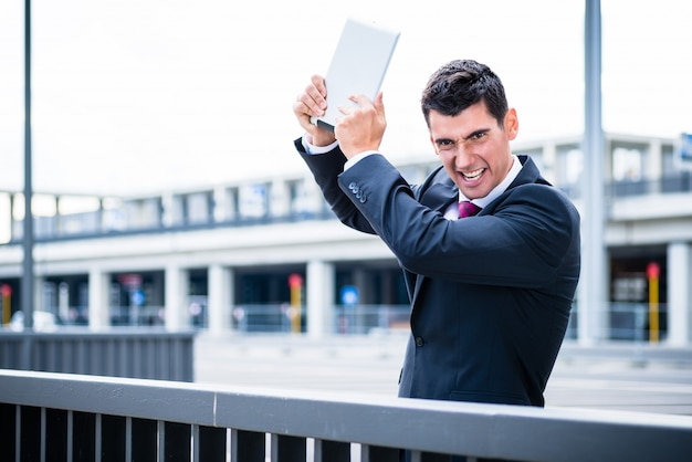 Verärgerter geschäftsmann mit tablet-computer