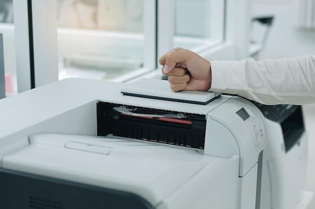 Verärgerter geschäftsmann schlägt seine faust auf druckerscanner oder laser-kopiermaschine im büro