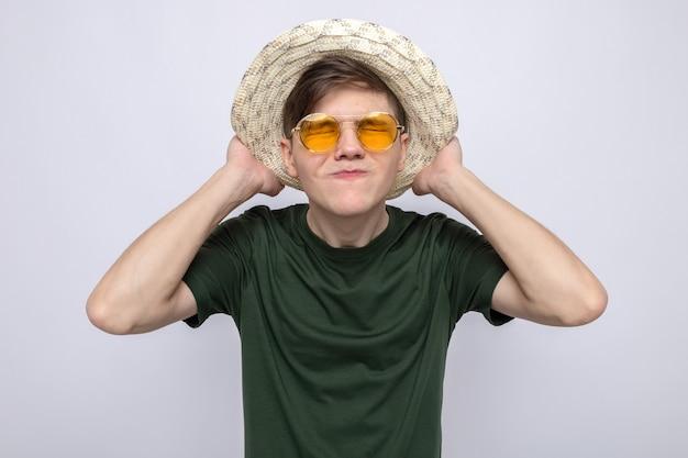 Verärgerter griff junger gutaussehender kerl mit brille mit hut