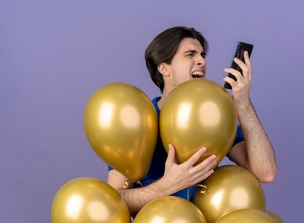 Verärgerter gutaussehender kaukasischer mann steht mit heliumballons, die das telefon halten und betrachten