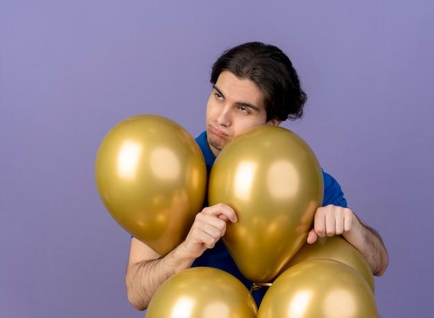 Verärgerter gutaussehender kaukasischer mann steht mit heliumballons und schaut auf die seite
