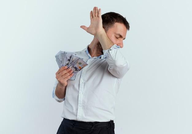 Verärgerter gutaussehender mann hält geld und hebt hand, das gesicht versteckt seite betrachtet auf weißer wand seite betrachtet