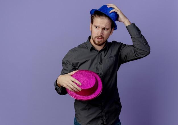 Verärgerter gutaussehender mann hält rosa hut und setzt auf blauen kopfhut auf lila wand auf