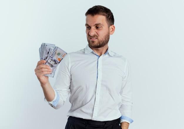 Verärgerter gutaussehender mann hält und betrachtet geld isoliert auf weißer wand