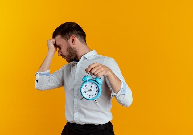 Verärgerter gutaussehender mann legt faust auf stirn und hält wecker, der seite betrachtet, die auf orange wand lokalisiert ist