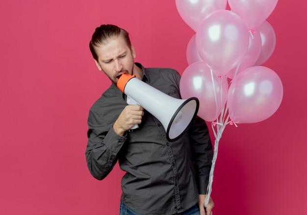Verärgerter gutaussehender mann steht mit heliumballons und schreit in lautsprecher, der auf rosa wand isoliert ist