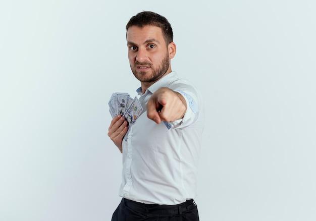 Verärgerter gutaussehender mann steht seitlich und hält geld und zeigt isoliert auf weiße wand