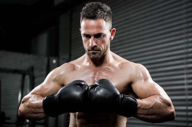 Verärgerter hemdloser mann mit boxhandschuhen an der crossfit turnhalle